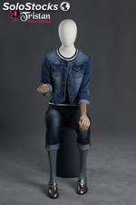 Faceless female mannequin sitting with articulable arms and hands.